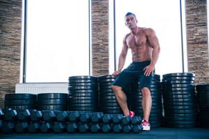Muscular man resting in gym