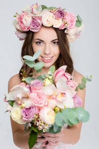 Lovely cheerful female in rose wreath showing bouquet of flowers