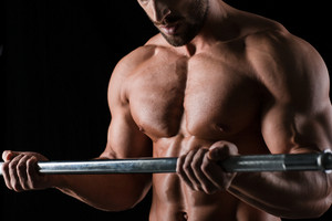 Muscular male body with barbell