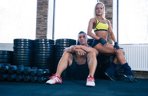 Woman and man resting in gym