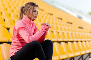 Woman in sports wear sitting on the chair at stadium