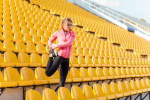 Woman stretching legs at stadium