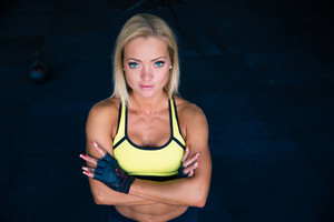 Sporty young woman with arms folded