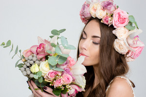 Attrative tender woman in roses wreath smelling bouquet of flowers