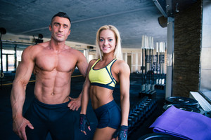 Smiling man and woman standing in gym