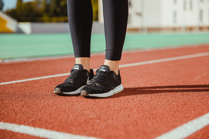 Female runner legs at stadium