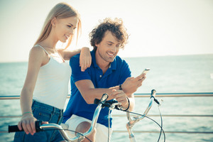 Man and woman on bicycle using smartphone together