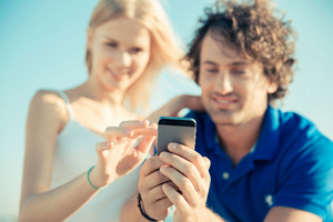 Happy couple using smartphone