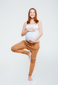 Smiling pregnant woman doing yoga exercise