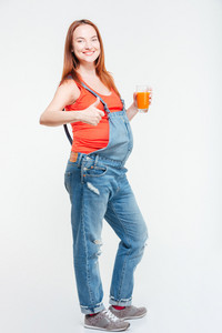 Happy woman showing thumb up and glass of orange juice