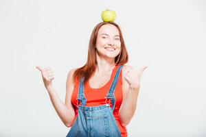 Pregnant woman with apple on head showing thumbs up