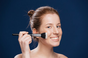 Smiling woman with cosmetic brush