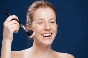 Laughing woman with cosmetic brush