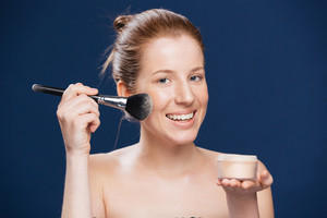 Smiling woman applying tonal cream