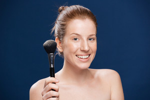 Happy woman holding makeup brush