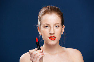 Attractive woman holding lipstick