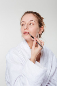 Woman applying lipstick with an applicator