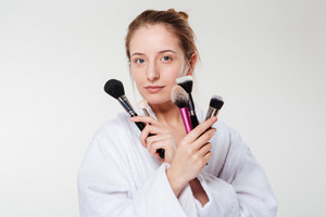 Beautiful woman holding makeup brushes