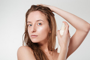 Attractive woman spraying hairspray