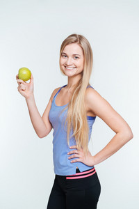 Smiling fitness woman holding apple