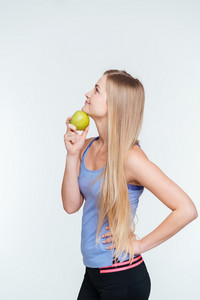 Pensive fitness woman holding apple