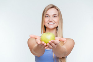 Smiling fitness woman giving apple at camera