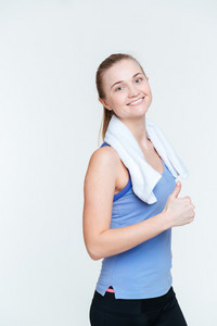 Smiling fitness woman showing thumb up