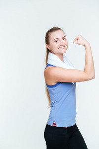 Smiling fitness woman showing her biceps