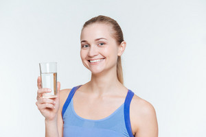 Smiling fitness woman holding glass with water