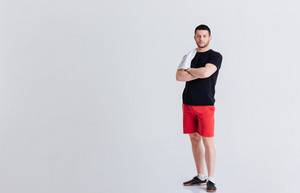 Fitness man standing with arms folded