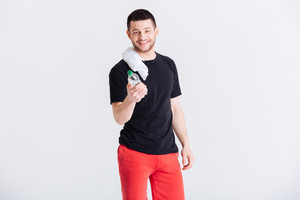 Smiling sports man holding bottle with water