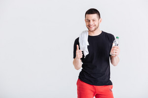 Sports man holding bottle with water and showing thumb up