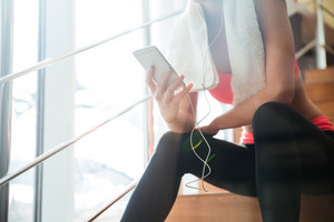 Sportswoman sitting and using smartphone with earphones in gym