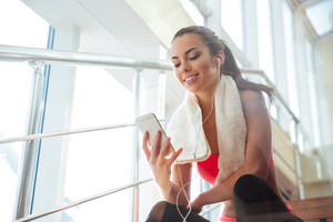 Cheerful woman sitting in gym and listening to music