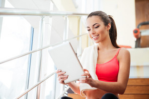 Happy cute young sportswoman using tablet in gym