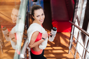 Cheerful cute woman athlete holding bottle of water in gym