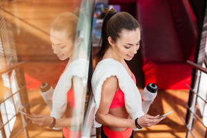 Smiling sportswoman drinking water and using smartphone in gym