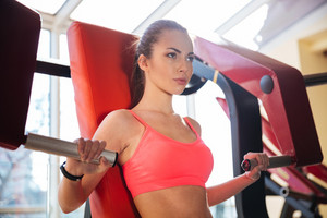 Concentrated beautiful young woman athlete training in gym