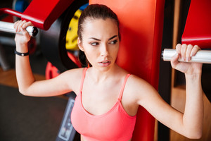 Attractive young sportswoman training arms muscles in gym
