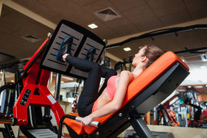 Attractive woman athlete training legs muscles in gym