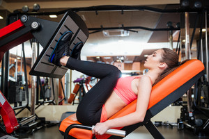 Strong sportswoman doing fitness exercises for legs muscles in gym