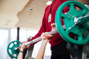 Hands of young sportswoman training with fitness instructor using barbell