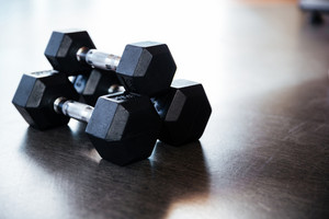 Three metal dumbbells on the floor in gym