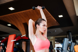 Serious sportswoman doing exercises for arms muscles using dumbbels