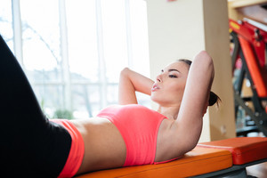 Serious sportswoman doing crunches on bench in gym