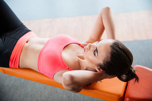 Focused sportswoman doing abs crunches on bench in gym