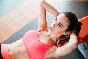 Concentrated woman athlete doing exercises lying on bench in gym