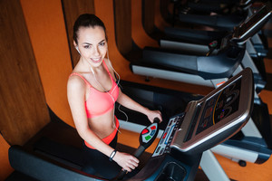 Cheerful sportswoman with earphones training on treadmill in gym