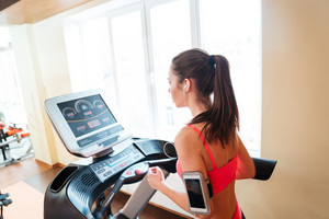 Beautiful woman athlete listening to music and running on treadmill