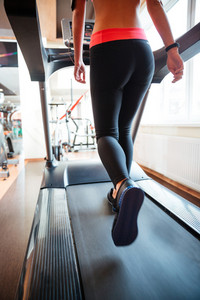 Attractive sportswoman running on treadmill in gym